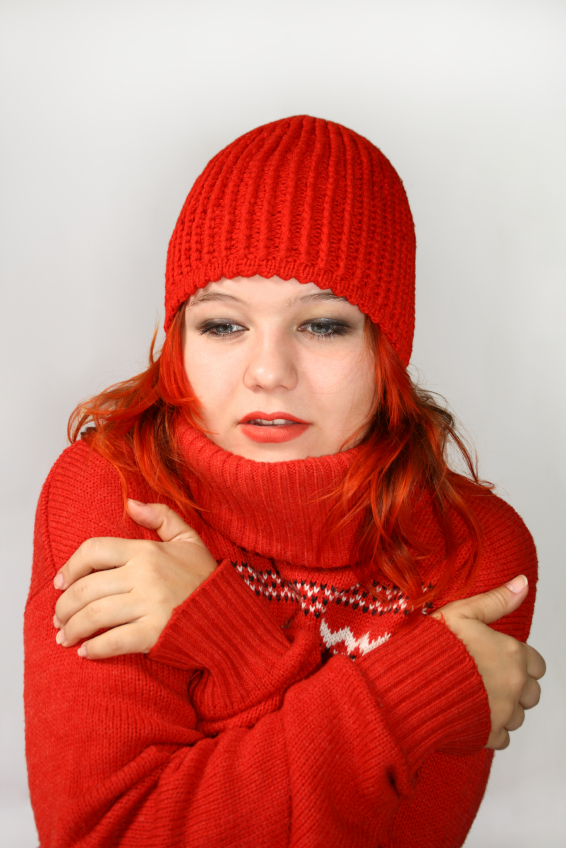 Young girl hides into the collar of the red sweater
